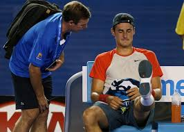 Tomic receiving treatment during the first round of the Aus Open 2014